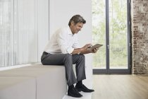Businessman sitting on bench in modern office and using tablet — Stock Photo