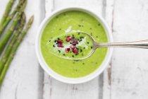 Зеленый спаржа суп с семенами граната и черным кунжутом на ложке, крупным планом — стоковое фото