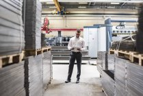 Businessman with tablet standing on factory shop floor — Stock Photo