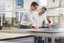 Два улыбающихся бизнесмена на фабрике смотрят на план — стоковое фото