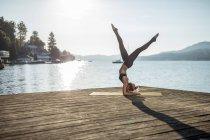 Женщина практикует йогу на пристани у озера — стоковое фото