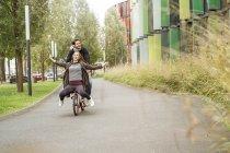 Heureux couple chevauchant sur un vélo sur une voie — Photo de stock