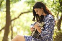 Mujer joven tocando la guitarra en el bosque - foto de stock