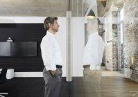 Зрелый бизнесмен, отражающийся в стеклянном стекле современного конференц-зала — стоковое фото