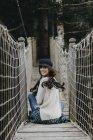 Портрет Усміхаючись молодої жінки, що сидить на підвісному мосту — стокове фото