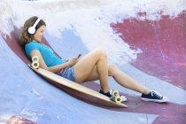 Longboard femminile con auricolari sdraiato in halfpipe — Foto stock