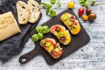 Bruschetta, ciabatta with multi-coloured tomatoes and basil — Photo de stock