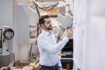 Uomo d'affari in fabbrica guardando il piano — Foto stock