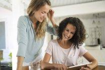 Deux femmes souriantes à la maison en utilisant une tablette — Photo de stock