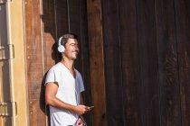 Jovem feliz com telefone celular e fones de ouvido encostados à parede de madeira — Fotografia de Stock
