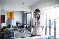 Молодой художник, работающий в своей мастерской, фотографирует свои работы на смартфоне — стоковое фото