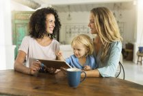 Two smiling women with a child using tablet at kitchen table — Stock Photo