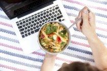 Uomo che mangia insalata di tagliatelle su una coperta in un parco, vista parziale — Foto stock