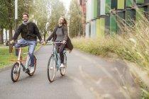 Joyeux couple à vélo main dans la main sur une voie — Photo de stock