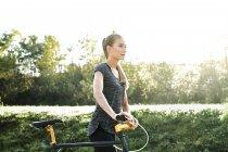 Спортивная молодая женщина с велосипедом на природе — стоковое фото