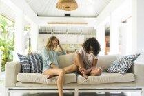 Два щасливих жінок весело разом на дивані — стокове фото