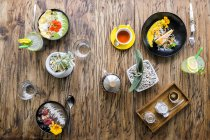 Variation of exotic decorated food on wooden tale — Stock Photo