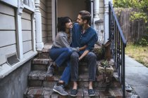 Happy couple sitting on stoop stairs embracing — Stock Photo