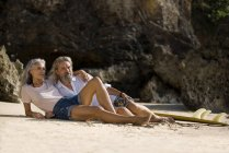Bellissima coppia anziana con tavola da surf sdraiata sulla spiaggia — Foto stock