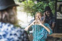 Schöne junge Frau, die ein Fingerrahmenherz macht und ihren Freund durch ein Fenster anlächelt — Stockfoto