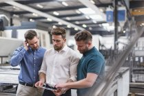 Трое мужчин делятся планшетом на заводе — стоковое фото