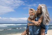 Pares sênior consideráveis que têm o divertimento na praia — Fotografia de Stock