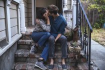 Couple sitting on stoop stairs and kissing — Stock Photo