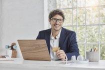 Retrato de homem de negócios sorridente com laptop na mesa segurando cartão de crédito — Fotografia de Stock