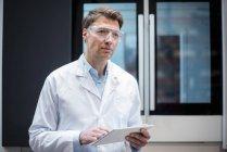 Portrait d'un homme portant un manteau de laboratoire et des lunettes de sécurité tenant une tablette à la machine — Photo de stock