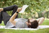 Homem deitado no cobertor em um parque lendo uma carta — Fotografia de Stock