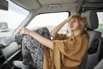 Молодая женщина с взъерошенными волосами сидит в машине — стоковое фото