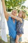 Menina feliz e mãe pendurado lavanderia no varal — Fotografia de Stock
