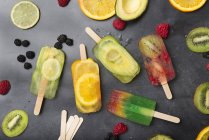Popsicles et fruits de fruit divers sur le fond gris — Photo de stock
