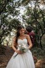 Наречений цілує усміхнений наречена в лісі — стокове фото