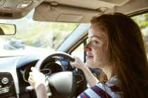 Smiling young woman with freckles driving car looking sideways — Stock Photo