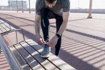 Спортивный человек шнурки свои ботинки на скамейке — стоковое фото