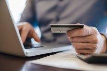 Mann mit Laptop und Kreditkarte in der Hand, Nahaufnahme — Stockfoto