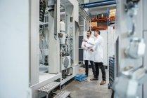Dois homens usando casacos de laboratório falando na fábrica — Fotografia de Stock