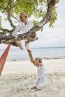Таиланд, острова Пхи Пхи, Ко Пхи Пхи (Ko Phi Phi), игривый мальчик и маленькая девочка залезают на дерево на пляже — стоковое фото