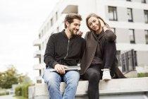 Pares felizes com o portátil no cerco urbano — Fotografia de Stock