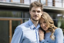 Portrait of smiling affectionate couple in front of their home — Stock Photo