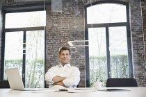 Porträt eines gestandenen Geschäftsmannes mit Laptop im modernen Büro — Stockfoto