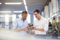 Два бизнесмена на заводе обсуждают продукт — стоковое фото