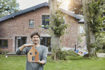 Portrait of man in garden of his home holding house model with woman in background lying in hammock — Stock Photo