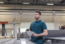 Man with tablet on factory shop floor looking around — Stock Photo