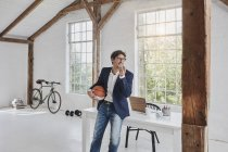 Businessman with basketball ball using smartphone in penthouse — Stock Photo