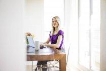 Портрет улыбающейся деловой женщины, работающей на ноутбуке — стоковое фото