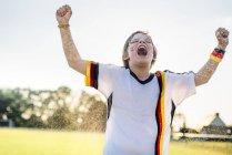 Мальчик в немецкой футбольной рубашке кричит от радости, стоя в воде брызги — стоковое фото