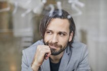 Retrato de hombre de negocios guapo barbudo en la ventana, mano en la barbilla - foto de stock
