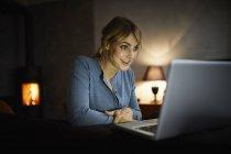 Ritratto di donna stupita che usa il computer portatile a casa la sera — Foto stock